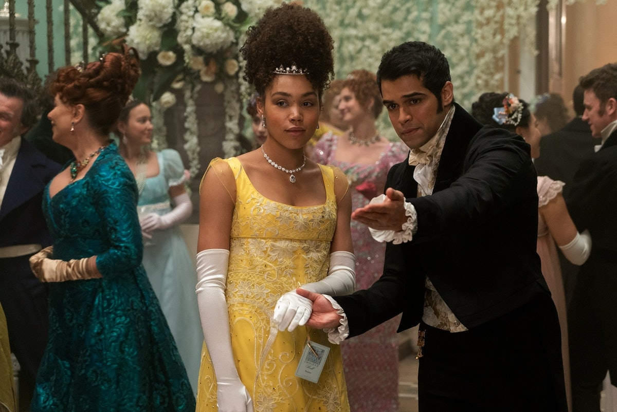 Marina from 'Bridgerton,' who is wearing a yellow gown, is led by hand to the dance floor by a smitten suitor.