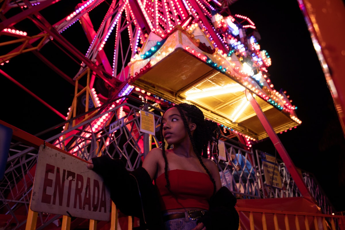 February 1 horoscope, young woman in front of ferris wheel, ride