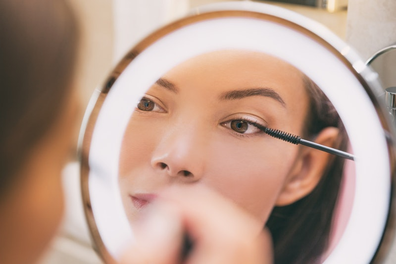 woman applying mascara in front of a mirror — starting with a waterproof formula is a way to avoid making mascara mistakes.