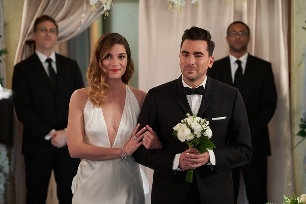 Alexis and David from 'Schitt's Creek' lock arms as they walk down the aisle at David's wedding.