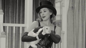 Elizabeth Olsen holding a white rabbit in WandaVision