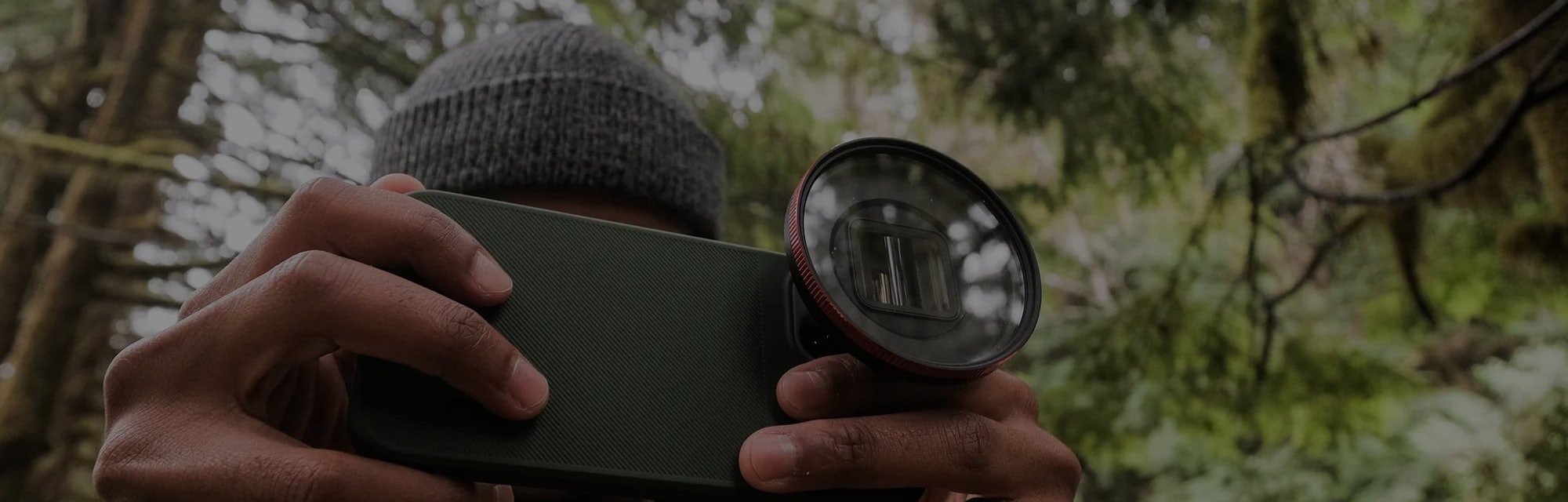 A man holding a smartphone with an attached add-on lens.
