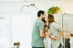 couple sweetly kissing in kitchen, holding infant between them