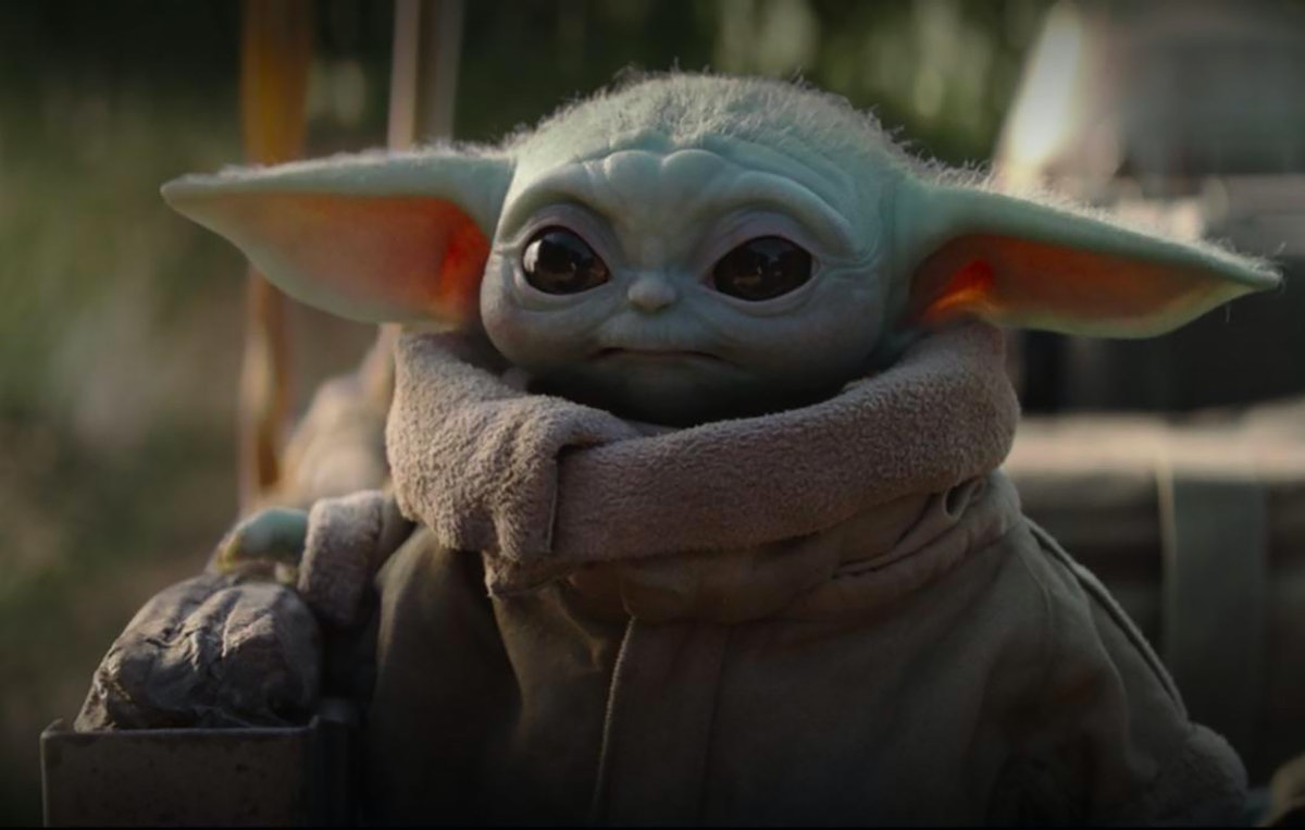Baby Yoda stares off into the distance in his cozy robe.