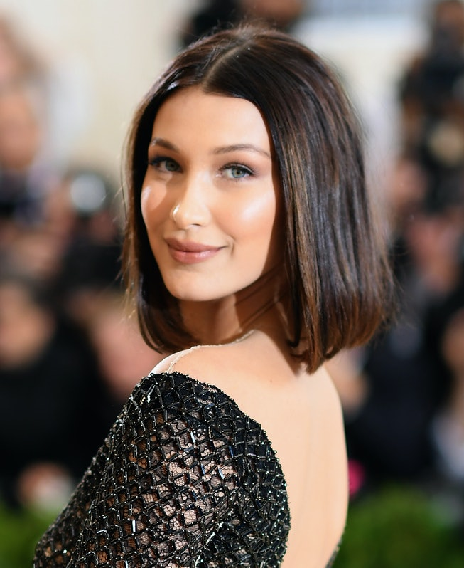 Bella Hadid, with a shoulder-length brunette bob, poses with a smile