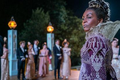 Adjoa Andoh as Lady Danbury on Bridgerton looks in the distance wearing an ornate purple gown and tiara.