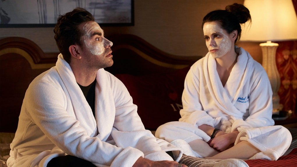 Stevie Budd and David Rose sit in bed wearing matching face masks and robe for a BFF night.
