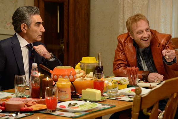 Roland Schitt and Johnny Rose sit a dining room table together for dinner in 'Schitt's Creek.'