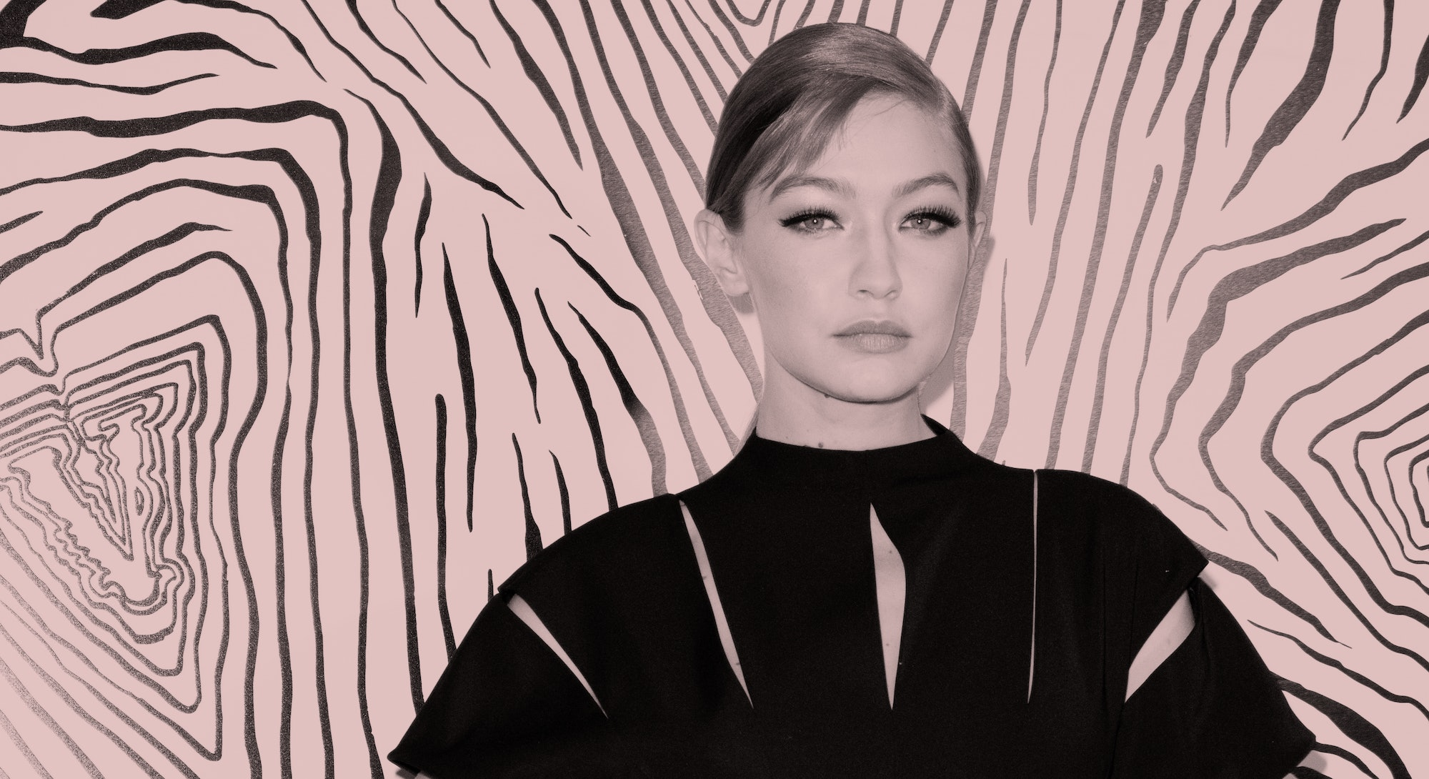 Gigi Hadid poses in a black dress, her hair pulled back in a tight bun.