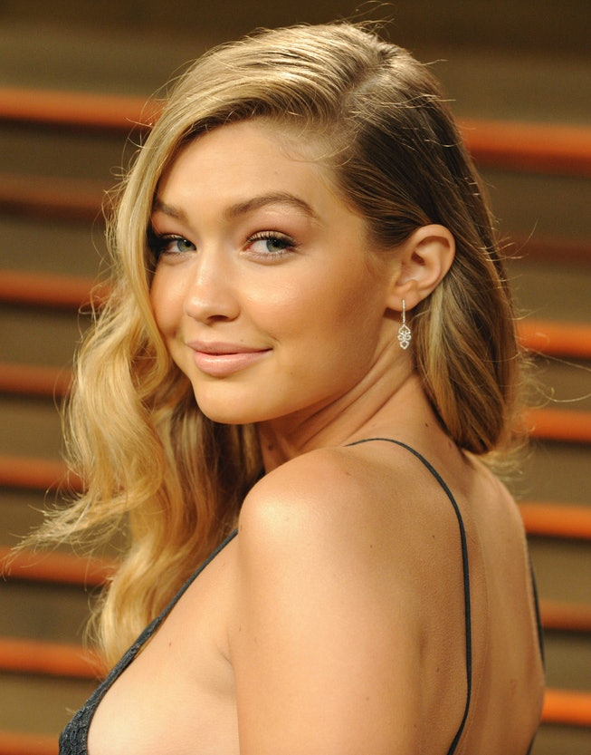 Gigi Hadid, wearing a black spaghetti strap dresses, turns to face the camera.