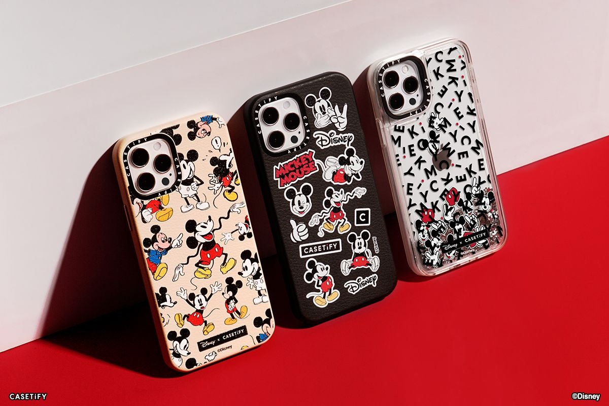Three phone cases from the Disney x CASETiFY collection lean up against a wall, and sport old designs of Mickey Mouse.