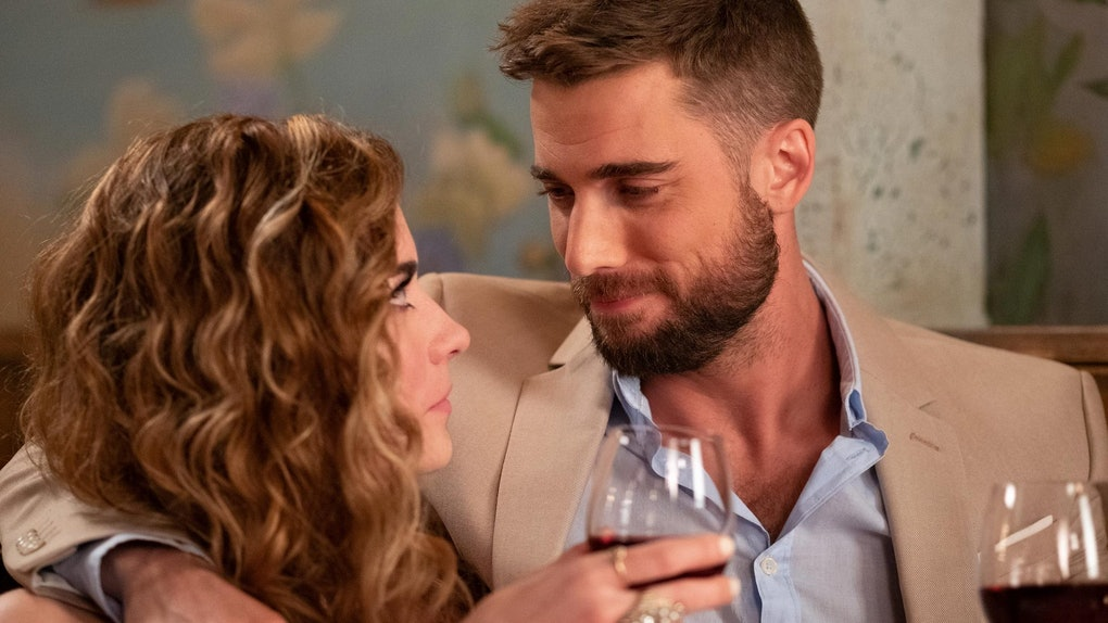 "Alexis and Ted from ""Schitt's Creek' hold wine glasses while looking into each other's eyes at a café."