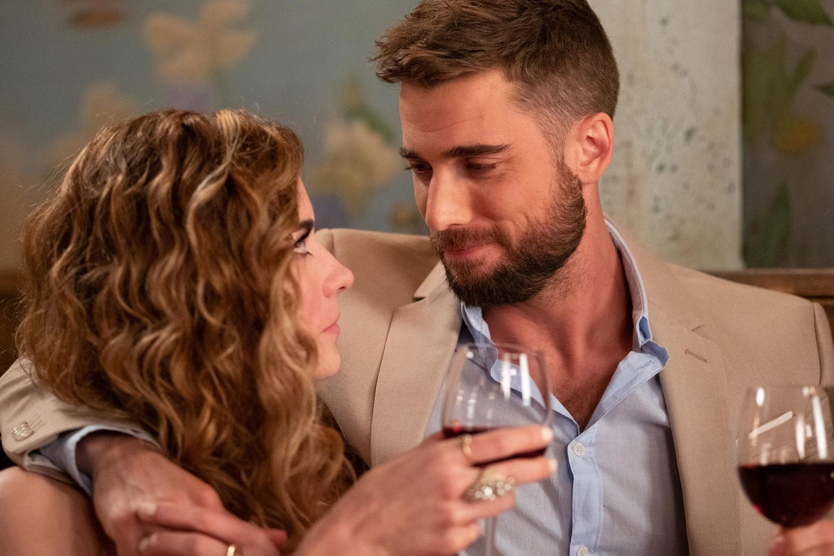 """Alexis and Ted from """"Schitt's Creek' hold wine glasses while looking into each other's eyes at a café."""