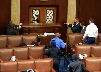 U.S. Capitol police officers point their guns at a door that was vandalized in the House chamber dur...
