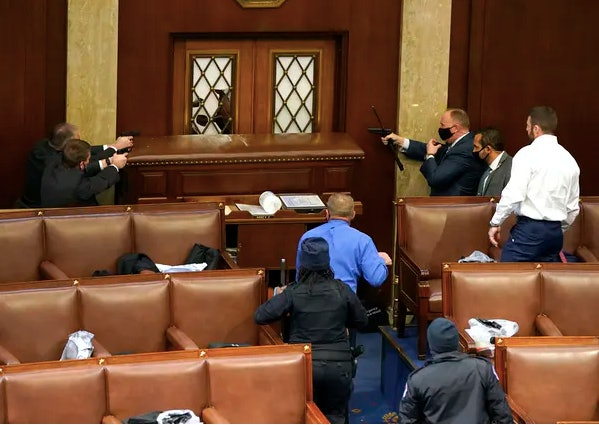 U.S. Capitol police officers point their guns at a door that was vandalized in the House chamber during a joint session of Congress on Wednesday in Washington, D.C.