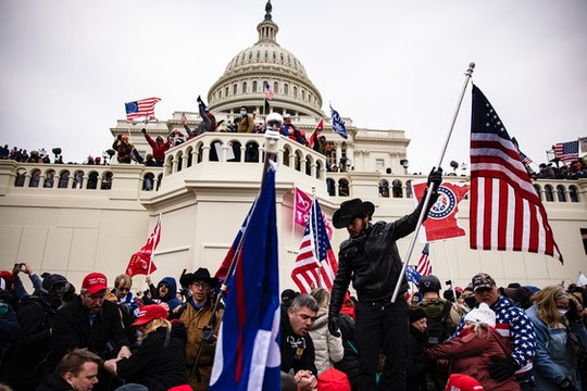 Trump supporters clash with police and security forces, climbing scaffolding as they try to storm the US Capitol in Washington D.C on January 6, 2021.
