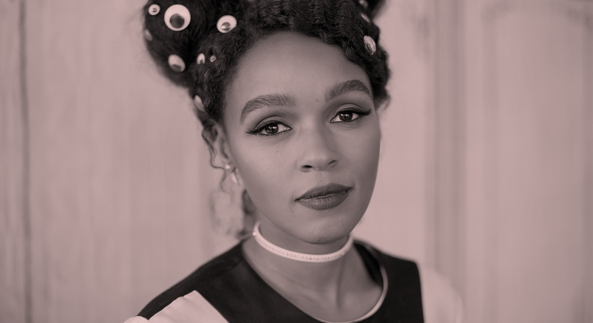 Janelle Monae, wearing her hair in two braided space buns that featured eye stickers, smiles at the camera