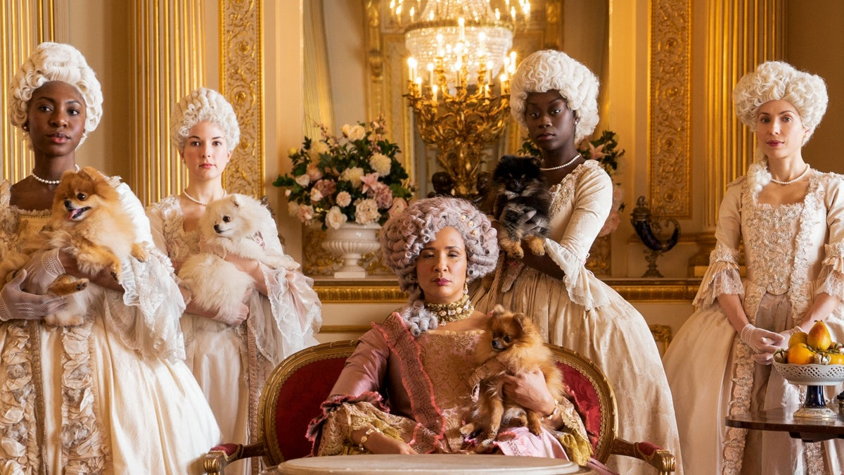 The queen in 'Bridgerton' sits with her dog, surrounded by ladies with dogs.