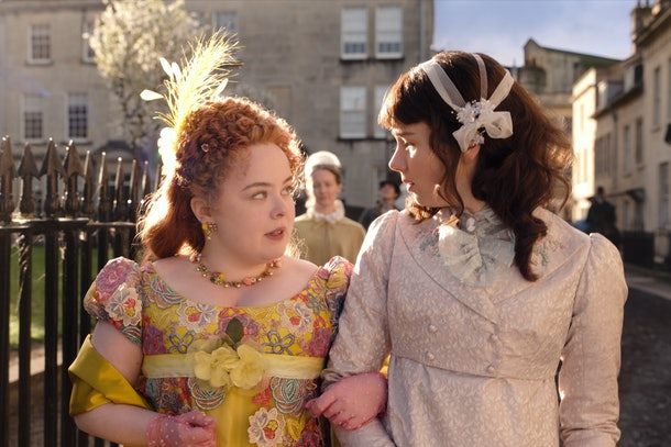 Eloise and Penelope from 'Bridgerton' look at each other while they chat and cross arms for a sunny afternoon stroll.