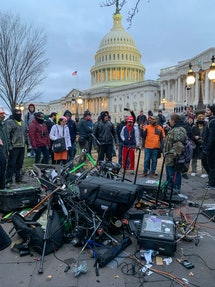 People stand around media equipment destroyed by Trump supporters outside the US Capitol in Washington DC on January 6, 2021.