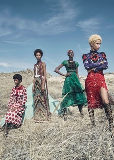 four models wearing dresses in a grassy field