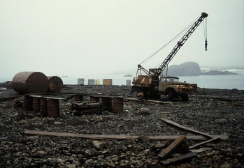 An old ZIL-130 truck, rusting drums, and other refuse litter the shoreline at Bellingshausen, a Russ...