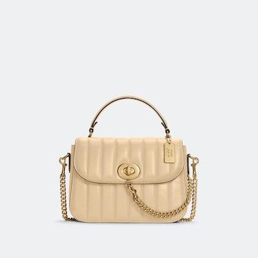 Jennifer Lopez X Coach quilted cream colored top handle satchel.