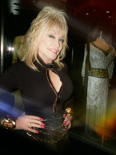 Dolly Parton wears a Louis Vuitton bodysuit, long shorts, and chunky gold-tone necklaces (worn as be...