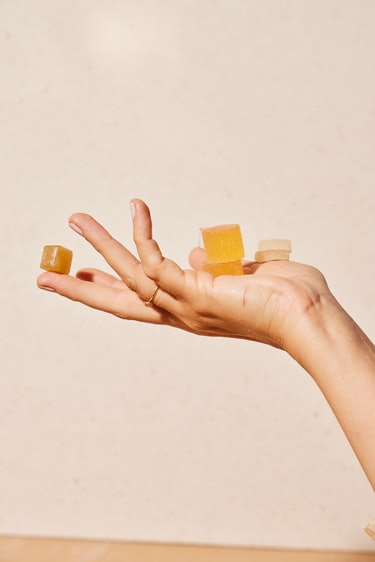 hand holding gummies, artfully arranged in front of a white background