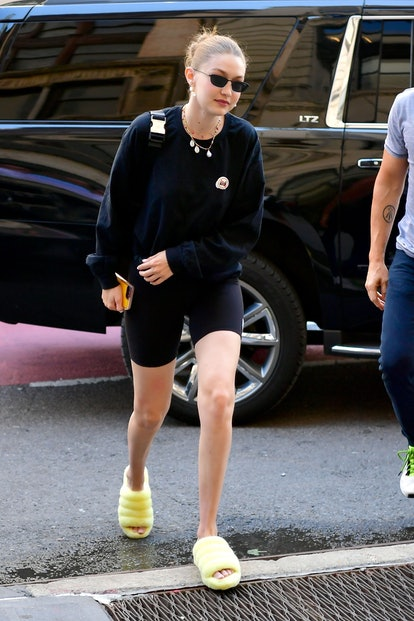 Gigi Hadid wears neon yellow UGG Fluff Yeah slippers and Prada nylon belt bag while out and about in...