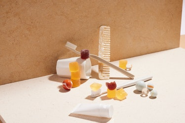 bathroom items, like a cup, toothbrush and a comb, artfully arranged with some gummies