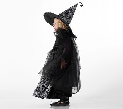 Toddler girl posing in witch costume