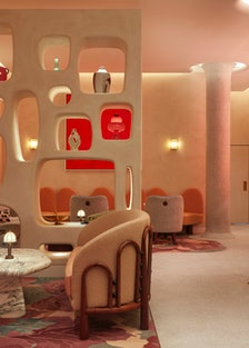 a dimly lit, modernist bar featuring artwork in various shades of red