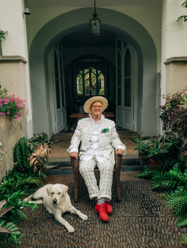 مانولو بلانیک که در عکس با سگ قرار دارد ، لباس و لوازم جانبی خود را می پوشد.