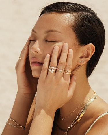 Models wears stacked rings, necklaces, and earrings from Aurate New York.