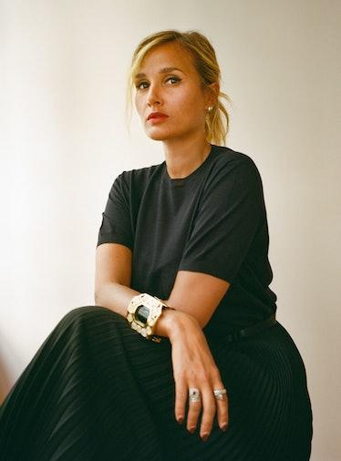 Director Julia Ducournau wears black dress and jewelry.
