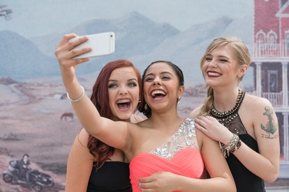 Young group of sorority sisters posing for a selfie at their college's fall semi-formal celebration,...