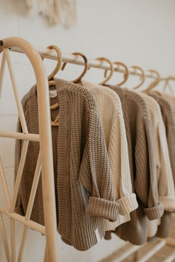 knit cardigans on hangers; hanging on clothing rack