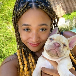 Naomi Osaka in braids and beads with her puppy