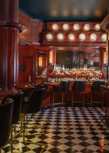 the inside of an old-fashioned bar, with wood panelling and black and white floors