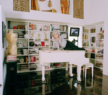 Rita Moreno lies atop a white piano in black pants and gray top surrounded by bookshelves.