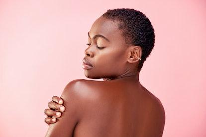 Woman touching bare shoulder