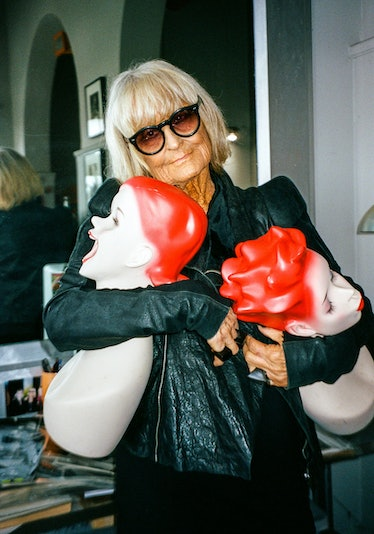 Barbara Hulanicki wears sunglasses holding two red-headed mannequin heads.