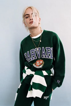 Zara model wears preppy Harvard sweater, joggers, and striped rugby.
