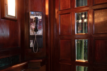 یک تلفن پرداخت در غرفه با روکش چوبی
