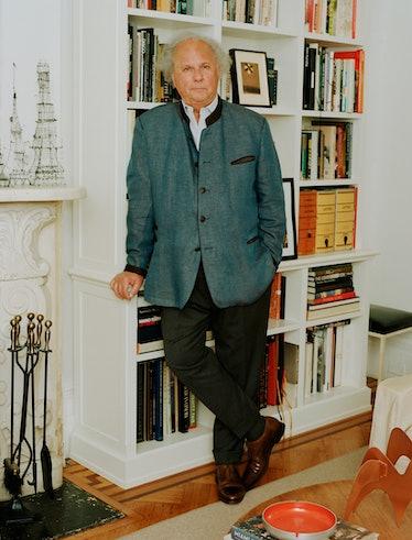 Graydon Carter poses against bookshelf in gray jacket and black pants.