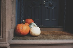 assorted fall pumpkins sitting on a front porch