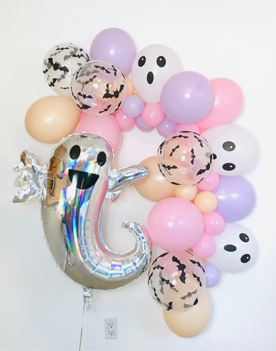 a Halloween balloon garland with pastel balloons and silver ghosts
