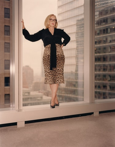 J Smith-Cameron stands in window in leopard skirt and black blouse.
