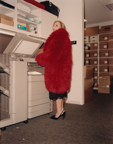 J Smith-Cameron in red coat at copy machine.